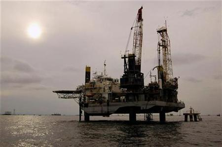 An oil facility is seen at Venezuela's Maracaibo lake, November 5, 2007. Rising oil prices could force more than three-quarters of Americans to tighten up their budgets by cutting fuel use or by slashing spending elsewhere, according to a Reuters/Zogby poll. REUTERS/Isaac Urrutia