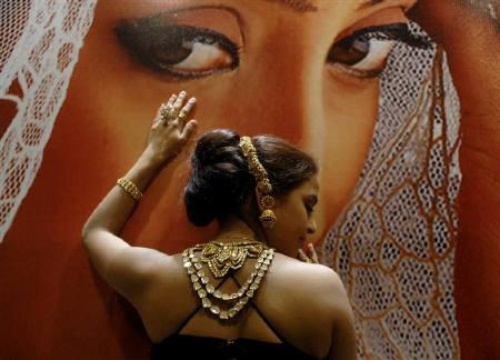 A model displays gold jewellery at a show in Hyderabad September 8, 2007. India's gold market saw little trading in the physical metal on Monday with profit-taking by investors denting local prices, dealers said. REUTERS/Krishnendu Halder/Files