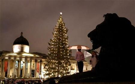 Two spectators stand on a statue to view the annual lighting of the Christmas tree in Trafalgar Square in central London, December 6, 2007. Hindus, Sikhs and Muslims joined the country's equality watchdog on Monday in urging people to enjoy Christmas without worrying about offending non-Christians. REUTERS/Toby Melville