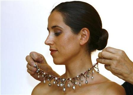 Christie's employee Linda Pyke is dressed with a necklace, made of pearls belonging to Marie Antoinette, at Christie's Auction House in London September 27, 2007. The pearls once belonging to Antoinette and taken to Britain by a friend for safekeeping failed to find a buyer at auction on Wednesday. REUTERS/Luke MacGregor