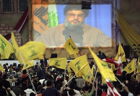 Hezbollah leader Sayyed Hassan Nasrallah speaks through a screen as supporters wave the group's flag during a rally to commemorate ''Martyr's Day'' in a Beirut suburb November 11, 2007. North Korea may have given arms to Lebanon's Hezbollah and Sri Lanka's Tamil Tigers, according to a report compiled for Congress that could complicate U.S. plans to drop Pyongyang from its terrorism blacklist. REUTERS/Issam Kobeisi