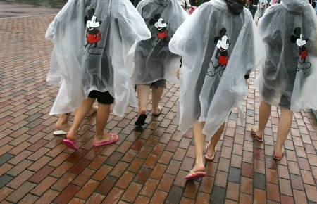 Visitors wear raincoats featuring Mickey Mouse at Hong Kong's Disneyland in this September 12, 2006 file photo. Attendance at Hong Kong Disneyland, which the government had already branded unsatisfactory, fell to just over 4 million in its second year, it said on Tuesday, representing a fall of more than 20 percent. REUTERS/Paul Yeung