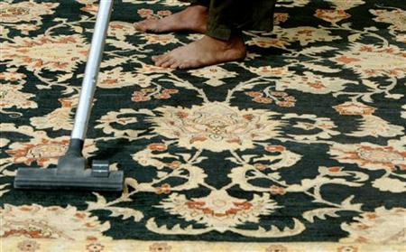 A man vacuums a carpet in this October 10, 2004 file photo. Vacuum cleaners kill fleas just as well as any poison, surprised U.S. researchers said on Tuesday. REUTERS/Caren Firouz