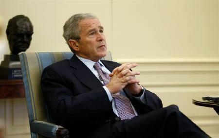 U.S. President George W. Bush looks up during an interview with Reuters reporters in the Oval Office of the White House in Washington January 3, 2008. Bush said on Saturday he would use part of a weeklong Middle East trip next week to press allies to help keep Iran's ''aggressive ambitions'' in check. REUTERS/Kevin Lamarque
