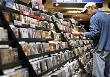 A man looks at music CDs inside the Virgin Megastore in New York November 26, 2007. Expectations for the weakest consumer spending performance in 17 years during 2008 kept the odds of a recession at nearly 40 percent, a survey of top forecasters showed on Thursday. REUTERS/Shannon Stapleton