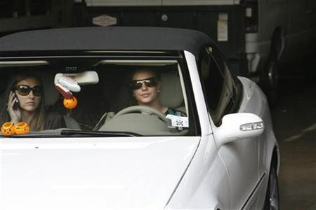 Britney Spears drives her Mercedes-Benz with her assistant Alli Simms (L) as she leaves the Stanley Mosk Courthouse garage after a child custody hearing with her ex-husband regarding her two sons in Los Angeles, California October 26, 2007. Four photographers were arrested for reckless driving after a late night car chase of Spears on the outskirts of Los Angeles, police said on Thursday. REUTERS/Fred Prouser