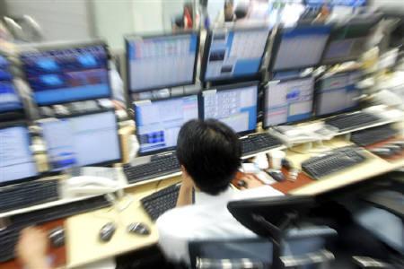 1月22日、東京市場午前の取引では、日経平均株価が前日比で一時600円程度下げ、リスク回避の動きを背景に主要通貨売り/円買いが進んだ。写真は2004年2月、都内のディーリングルームで撮影したとレーダー(2008年 ロイター/Yuriko Nakao)