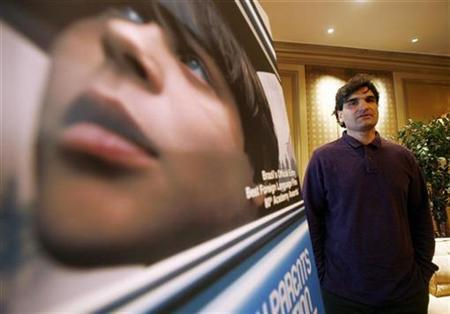 Cao Hamburger, Brazilian director of the movie ''The Year My Parents Went on Vacation,'' poses next to the movie's poster in New York, December 4, 2007. Some of 2007's most acclaimed international films will not be competing for the foreign-language prize at the Academy Awards next month. REUTERS/Shannon Stapleton