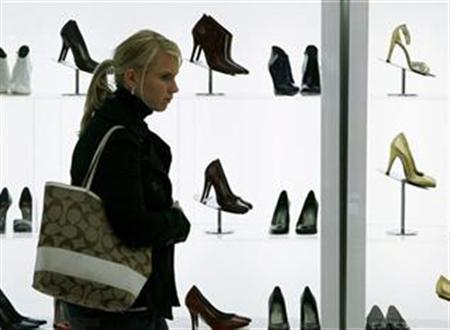 A woman looks at shoes while shopping in New York, November 20, 2007. In the latest example that the U.S. dollar just ain't what it used to be, some shops in New York City have begun accepting euros and other foreign currency as payment for merchandise. REUTERS/Lucas Jackson
