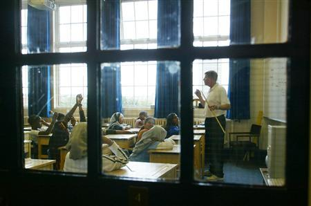 Head teacher Chris Hassell teaches a class at Taylor Primary School in Leicester in this file photo. Starting school at the age of four is ''stressful'' to children and does not help their education, according to a major review of English primary schools which also concluded kids take too many tests too early. REUTERS/Darren Staples