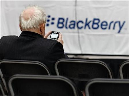 A shareholder uses his Blackberry while waiting for the Research In Motion annual meeting to begin in Waterloo, Ontario, July 17, 2007. Research In Motion said on Tuesday it is too soon to determine the cause of a massive BlackBerry service outage that left subscribers across the Americas with spotty or non-existent access to wireless e-mail for about three hours on Monday. REUTERS/J.P. Moczulski