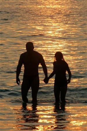 A couple walk in the sea and enjoy the sunset on Patong beach, in the Thai resort island of Phuket, March 24, 2005. Alarmed by polls showing one in four Thai teens will celebrate St. Valentine's Day by having sex, police plan to swoop on motels, malls and parks to ensure youths behave themselves on the ''Day of Love.'' REUTERS/Sukree Sukplang