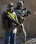 <p>Солдат армии США и служащий внутренних гражданских сил Ирака в городе Байджи на севере страны, 27 декабря 2007 года. США, планирующие к июлю вывести из Ирака четверть своих боевых соединений, надеются продолжить вывод войск, но после двухмесячной паузы для оценки последствий сокращения военного присутствия в оккупированном ближневосточном государстве, сказал министр обороны США Роберт Гейтс. REUTERS/Bob Strong</p>
