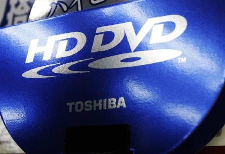 A silhouette of a shopper is reflected in an advertisement board of Toshiba Corp's HD DVD in Tokyo February 18, 2008. DreamWorks Animation SKG Inc said on Tuesday it was locked in an exclusive deal to distribute DVDs on Toshiba Corp's HD DVD format even though the Japanese electronics maker plans to quit the technology. REUTERS/Issei Kato