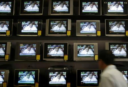 A man looks at TV screens showing Finance Minister Palaniappan Chidambaram presenting the Union budget, at a shop in Mumbai February 29, 2008. REUTERS/Punit Paranjpe