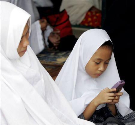 3月4日、フィリピン人が昨年送った携帯電話メッセージの1日当たりの平均数が10億通に倍増したことが分かった。写真は2004年10月にマニラで撮影した携帯メッセージを送るフィリピン人少女(2008年 ロイター/Erik de Castro)