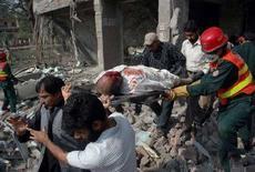 <p>Спасатели выносят раненого с места взрыва в городе Лахор 11 марта 2008 года. В результате двух взрывов в пакистанском городе Лахор во вторник погибли 24 человека, сообщила полиция. (REUTERS/Mohsin Raza)</p>