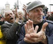 <p>Люди выкрикивают лозунги во время митинга оппозиции у здания парламента в Тбилиси. 10 марта 2008 года. Парламент Грузии в среду утвердил конституционные поправки об изменениях в избирательном законодательстве, несмотря на возражения ряда депутатов, в знак протеста третий день продолжающих голодовку в здании. (REUTERS/David Mdzinarishvili)</p>