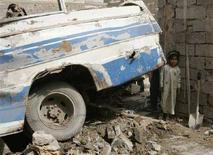 <p>Imamgine d'archivio di una bambina irachena dietro un veicolo distrutto a Baghdad. REUTERS/Kareem Raheem (IRAQ)</p>