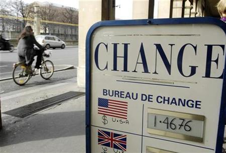 A woman pedals near by a currency exchange bureau in Paris February 27, 2008. REUTERS/Gonzalo Fuentes