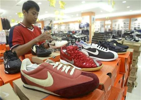 A worker holds a Nike shoe at a shopping mall in Jakarta July 17, 2007. Nike  Inc, the world's biggest sneaker and sportswear maker, said falsified  documents ...