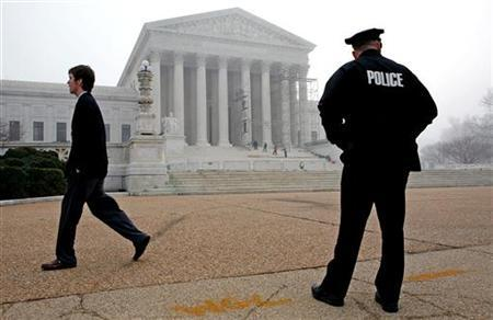 A police officer patrols in front of the Supreme Court building January 13, 2006. REUTERS/Joshua Roberts