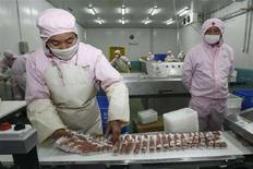 <p>Un'operaia lavora dei pezzi di carne di maiale a Wuhan, nella provincia Hubei. REUTERS/Stringer (CHINA)</p>