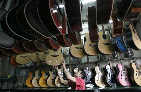A worker at a guitar shop hangs a new locally made instrument in Manila November 12, 2007. REUTERS/Cheryl Ravelo