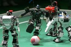 <p>Dei robot telecomandati giocano a calcio, a Tokyo. REUTERS/Toru Hanai</p>