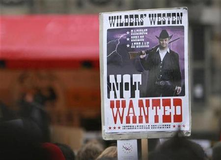 Demonstrators hold a placard of Geert Wilders during a protest against the Dutch politician and anti-Islam film-maker at Dam square in Amsterdam March 22, 2008. REUTERS/Ade Johnson