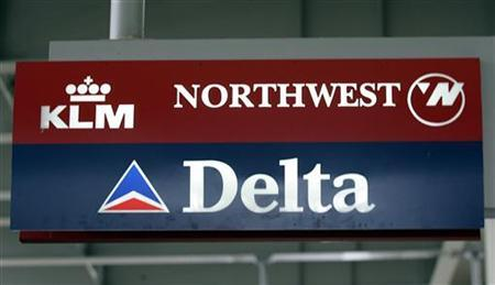 A Delta Airlines and Northwest Airlines sign hang at the arrival terminal at Detroit Metropolitan Airport in Romulus, Michigan September 14, 2005. REUTERS/Rebecca Cook