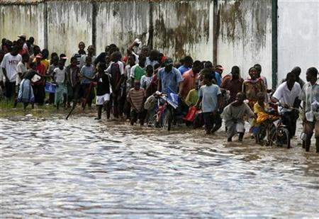 People walk through a flooded area to watch the Olympic torch relay in Dar es Salaam April 13, 2008. The Indian Ocean port hosted the Tanzanian leg of the Olympic torch relay this weekend. REUTERS/Radu Sigheti