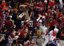"""<p>Болельщики клуба Национальной хоккейной лиги """"Монреаль Канадиенс"""" радуются одной из шайб, заброшенных их любимцами в ворота """"Бостона"""" в Бостоне 13 апреля 2008 года. Празднование болельщиками клуба Национальной хоккейной лиги """"Монреаль Канадиенс"""" выхода своей команды в следующий раунд плей-офф переросло в погромы и грабеж магазинов, а завершилось поджогами полицейских автомобилей и арестом наиболее буйных хоккейных фанатов. (REUTERS/Brian Snyder)</p>"""