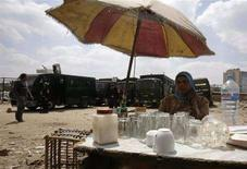 <p>امرأة مصرية تبيع الشاي وخلفها قوات أمن متمركزة في أحد شوارع مدينة المحلة الكبرى يوم 8 ابريل نيسان 2008 بعد مواجهات بين الشرطة ومحتجين. تصوير: ناصر نوري - رويترز</p>