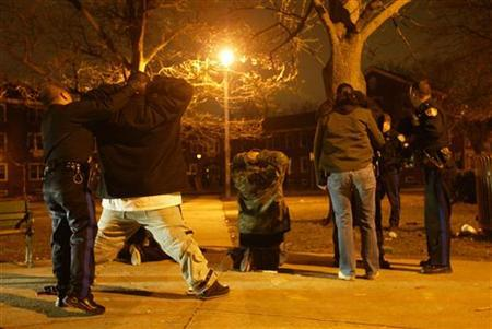 Camden police department officers search suspects in a night raid in Camden, New Jersey March 24, 2005. REUTERS/Shannon Stapleton