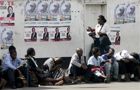 A woman carrying her child walks past people queuing to withdraw cash from a city bank in Harare May 6, 2008. REUTERS/Philimon Bulawayo