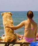 <p>Una donna abbraccia il suo cane guardando il mare dalla spiaggia di Maccarese (Roma) in una foto d'archivio. REUTERS/Alessia Pierdomenico AMP/AH/CRB</p>