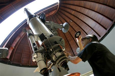 Father Emmanuel Carreira operates the telescope at the Vatican Observatory in Castelgandolfo, south of Rome, in this June 23, 2005 file photo. REUTERS/Tony Gentile