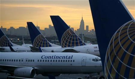 The Empire State Building on the New York skyline at sunrise is framed between airplanes at Liberty International Airport in Newark, New Jersey September 13, 2006. REUTERS/Gary Hershorn