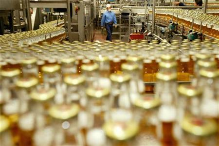 Hundreds of bottles of Mexico's world famous Corona beer surround a worker in the bottling line of Mexico City's Modelo brewery May 19, 2004. REUTERS/Andrew Winning