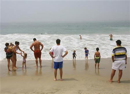 Tourists relax on a beach in Laguna Beach, California July 14, 2006. REUTERS/Lucas Jackson