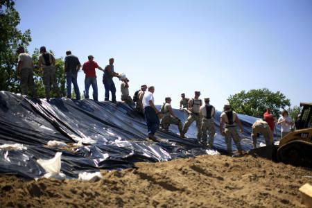 U.S. National Guard troops unload sandbags at a levee near the town of Hull, Illinois June 17, 2008. The swollen Mississippi River ran over the top of at least nine more levees on Wednesday as floodwaters swallowed up more U.S. farmland, feeding inflation fears as corn prices soared to record highs. REUTERS/Eric Thayer