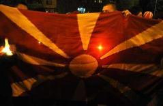 <p>Люди держат в руках флаг Македонии на акции протеста в Скопье 2 апреля 2008 года. Европейский союз потребовал от Македонии разрешить спор с Грецией относительно ее названия, для того, чтобы возобновить переговоры о вступлении в политический союз. (REUTERS/Ognen Teofilovski)</p>