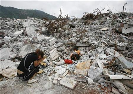 A grieving parent cries as she burns incense and her dead child's clothes in front of the rubble of the Beichuan Number One Middle School, located around 150 km (93 miles) north of Chengdu in Sichuan Province, June 12, 2008. REUTERS/David Gray