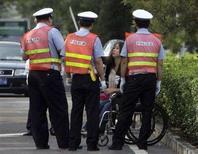 <p>In un'immagine d'archivio una donna cinese su una sedia a rotelle parla con alcuni agenti di polizia. REUTERS/David Gray</p>