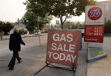 A woman walks past a sign featuring a gasoline sale at a filling station in Oakland, California June 24, 2008. REUTERS/Robert Galbraith