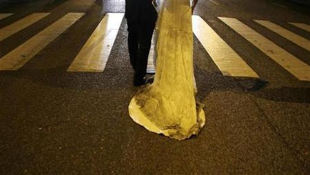 A couple walks as they get married under the patronage of Saint Antonio during a parade in Lisbon June 12, 2008. The Church of Sweden will carry out drive-in weddings lasting about seven minutes at a car rally next month in a bid to make marriage more accessible, it said on Thursday. REUTERS/Nacho Doce