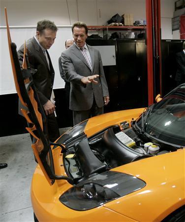 California Governor Arnold Schwarzenegger looks over the engine compartment of a Tesla Roadster with Tesla Motors Chairman Elon Musk in San Carlos, California June 30, 2008. REUTERS/Robert Galbraith