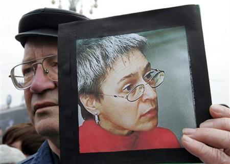 A man holds a portrait of Russian journalist Anna Politkovskaya in this file picture, during a rally in central Moscow October 8, 2006. REUTERS/Alexander Natruskin