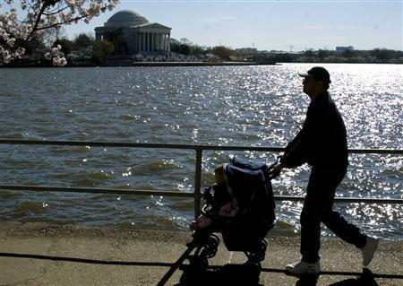 Taking in the sight of the Cherry Blossoms along the Tidal Basin, a man walks a baby in a stroller near the Jefferson Memorial (background), in Washington in this April 1, 2002 file photo. REUTERS/Kevin Lamarque